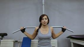 Giovane donna che flette i muscoli sulla macchina della palestra del cavo video d archivio