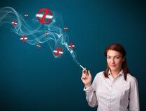 Giovane donna che fuma sigaretta pericolosa con i segni non fumatori Immagini Stock