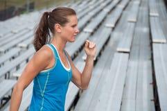Giovane donna che funziona sui Bleachers alla pista all'aperto Fotografia Stock Libera da Diritti
