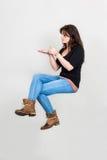 Giovane donna che galleggia nella posizione seduta con la presentazione del gesto Immagine Stock Libera da Diritti