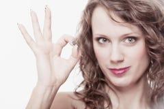 Giovane donna che gesturing il segno giusto giusto della mano Immagine Stock