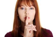 Giovane donna che gesturing per il quiet Immagine Stock