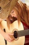 Giovane donna che gioca chitarra con l'espressione Fotografie Stock