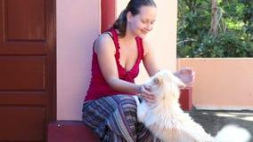Giovane donna che gioca con il cane stock footage