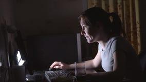 Giovane donna che gioca i giochi di computer con i chip e le bevande stock footage