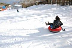 Giovane donna che gioca il gioco della neve Fotografie Stock
