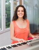 Giovane donna che gioca piano a casa Fotografia Stock