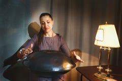 """Giovane donna che gioca su un primo strumento generationan chiamato tamburo di caduta """"o """"""""di caduta fotografia stock libera da diritti"""