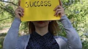 Giovane donna che giudica pezzo di carta giallo con successo compitato archivi video