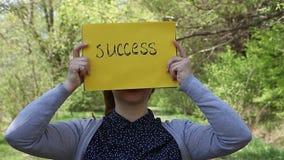 Giovane donna che giudica pezzo di carta giallo con successo compitato stock footage