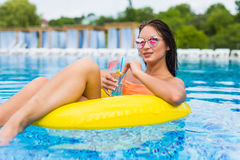 Giovane donna che gode con l'anello di gomma ed il cocktail nella piscina Immagine Stock