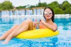 Giovane donna che gode con l'anello di gomma ed il cocktail nella piscina Fotografia Stock