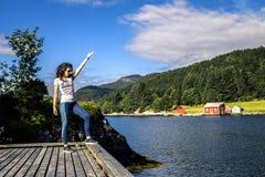 Giovane donna che gode del giorno soleggiato sul fiordo, Norvegia Fotografia Stock