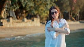 Giovane donna che gode del tramonto sulla spiaggia video d archivio