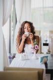 Giovane donna che gode dell'odore di caffè Fotografie Stock Libere da Diritti