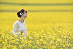Giovane donna che gode della musica nelle cuffie nella natura Fotografia Stock