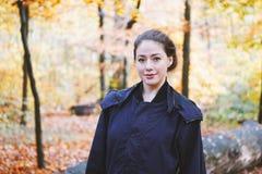 Giovane donna che gode della passeggiata attraverso la foresta in autunno fotografia stock