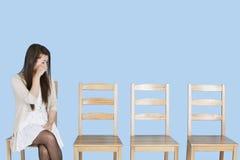 Giovane donna che grida oltre alle sedie di legno vuote sopra fondo blu fotografia stock libera da diritti