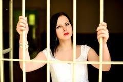 Giovane donna che guarda da dietro le barre Fotografie Stock Libere da Diritti