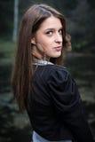 Giovane donna che guarda dietro la sua spalla Fotografia Stock