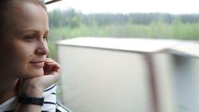 Giovane donna che guarda fuori la finestra del treno commovente archivi video