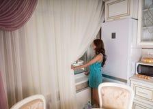 Giovane donna che guarda fuori la finestra della cucina Immagini Stock