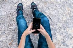 Giovane donna che guarda il suo smartphone su una roccia immagine stock