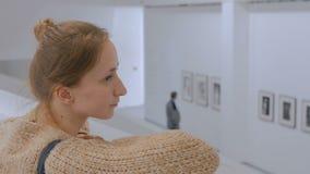 Giovane donna che guarda intorno nella galleria di foto moderna archivi video