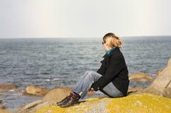 Giovane donna che guarda l'oceano Immagini Stock Libere da Diritti