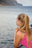 Giovane donna che guarda l'oceano su un'inferriata Immagini Stock