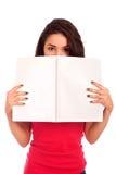 Giovane donna che guarda sopra la rivista Fotografia Stock