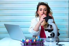 Giovane donna che guarda tramite un microscopio in laboratorio Fotografia Stock