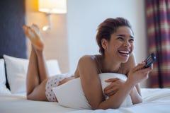 Giovane donna che guarda TV nella stanza Fotografia Stock
