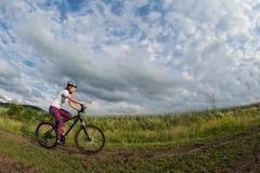 Giovane donna che guida la sua bici su una traccia rurale Fotografia Stock Libera da Diritti