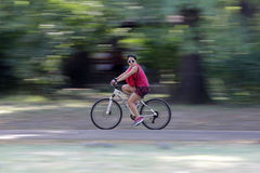 Giovane donna che guida una bici nel parco Immagine Stock