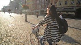 Giovane donna che guida una bicicletta in un quadrato di città, bello ciclismo alla via, vecchio fondo della ragazza della costru video d archivio