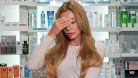 Giovane donna che ha febbre, sentendosi male, stante alla farmacia locale archivi video