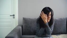Giovane donna che ha un naso semiliquido e che starnutisce facendo uso di un fazzoletto stock footage