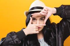 Giovane donna che incornicia il suo fronte con le sue dita Fotografie Stock Libere da Diritti