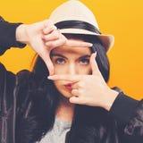 Giovane donna che incornicia il suo fronte con le sue dita Fotografia Stock