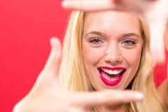 Giovane donna che incornicia il suo fronte con le sue dita Fotografia Stock Libera da Diritti