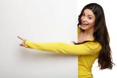 Giovane donna che indica il suo dito al bordo in bianco Immagini Stock Libere da Diritti