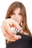 Giovane donna che indica le forbici alla macchina fotografica Immagine Stock