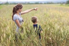 Giovane donna che indica mano e ragazzino suo figlio che sta nel whe Immagine Stock