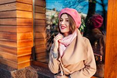 Giovane donna che indossa aria aperta d'avanguardia del berretto e del cappotto Vestiti ed accessori femminili della primavera Mo immagine stock