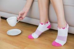 Giovane donna che indossa i calzini rosa che tengono una tazza Fotografie Stock Libere da Diritti