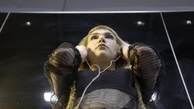 Giovane donna che indossa le piccole cuffie azione Vista dal basso delle cuffie d'uso della giovane epica attraente della donna c stock footage