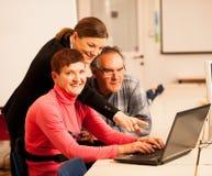Giovane donna che insegna alle coppie anziane delle abilità del computer Intergen Immagine Stock