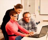 Giovane donna che insegna alle coppie anziane delle abilità del computer Intergen Fotografia Stock