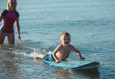 Giovane donna che insegna praticando il surfing suo figlio nell'oceano in un giorno soleggiato Fotografia Stock